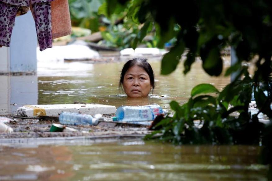 Una mujer camina por una calle sumergida de la ciudad de Hoi An (declarada Patrimonio de la Humanidad por la Unesco) después de que el tifón Damrey golpeara Vietnam en 2017.