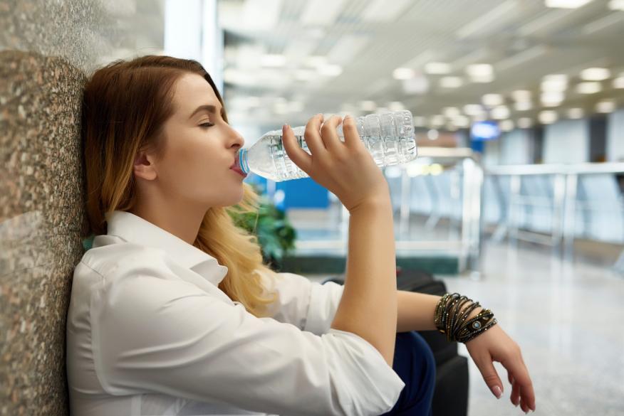 Una chica bebe agua de una botella de plástico en un aeropuerto