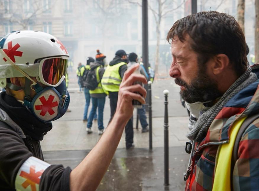 Un médico voluntario ayuda a un manifestante que sufre los efectos de los gases lacrimógenos disparado por la policía francesa, en el tercer acto de la protesta de los 'Gilets Jaunes' en París, este sábado 1 de diciembre.