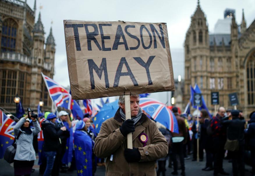 Un manifestante pro-Brexit sostiene una pancarta mientras los manifestantes en contra del Brexit se manifiestan fuera de las Casas del Parlamento en Londres, el 15 de enero de 2019.