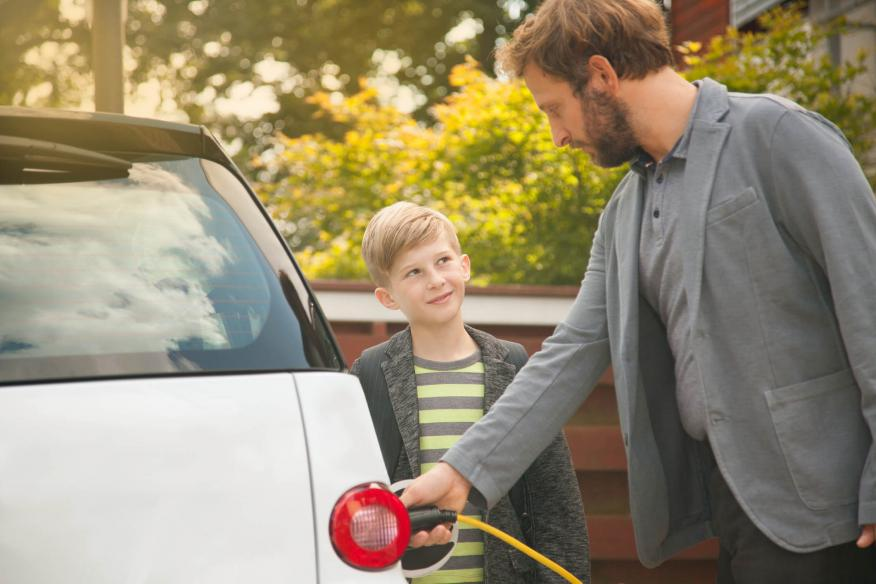 Familia cargando un coche eléctrico