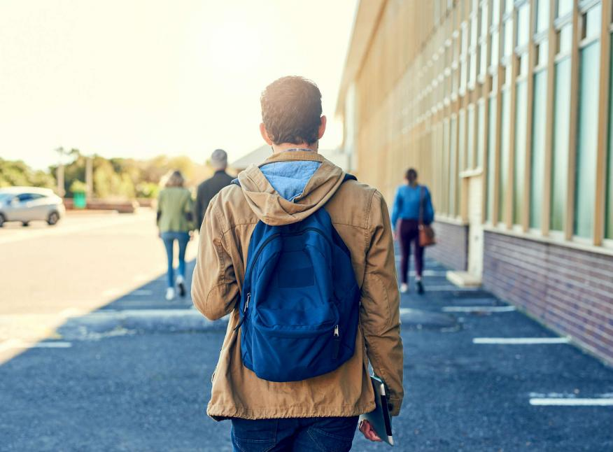 Un joven camina con su mochila a la espalda