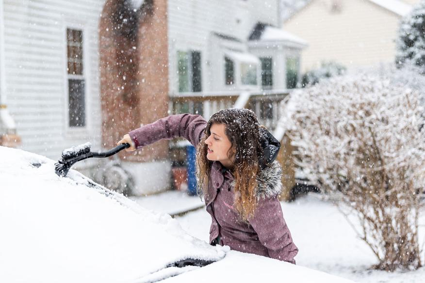 Una mujer retira el hielo de la luna de un coche