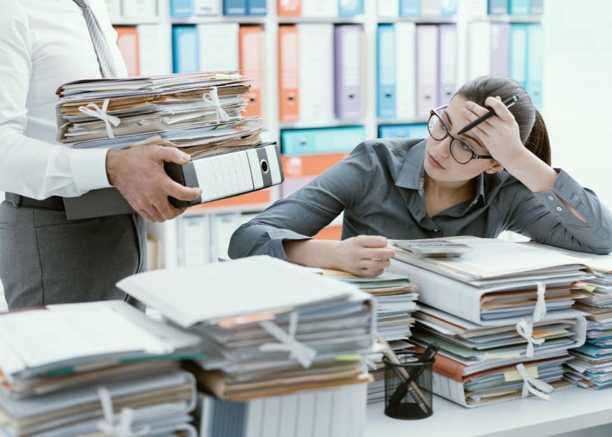 Una mujer mira con recelo el montón de documentos que le entrega su jefe.