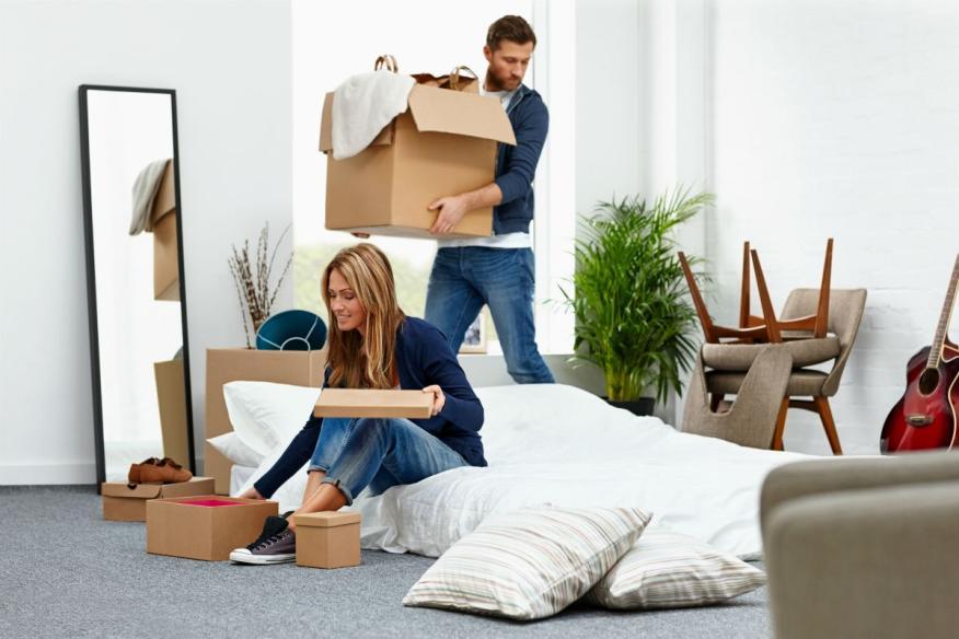 Una pareja desembala sus cajas en su nueva casa.