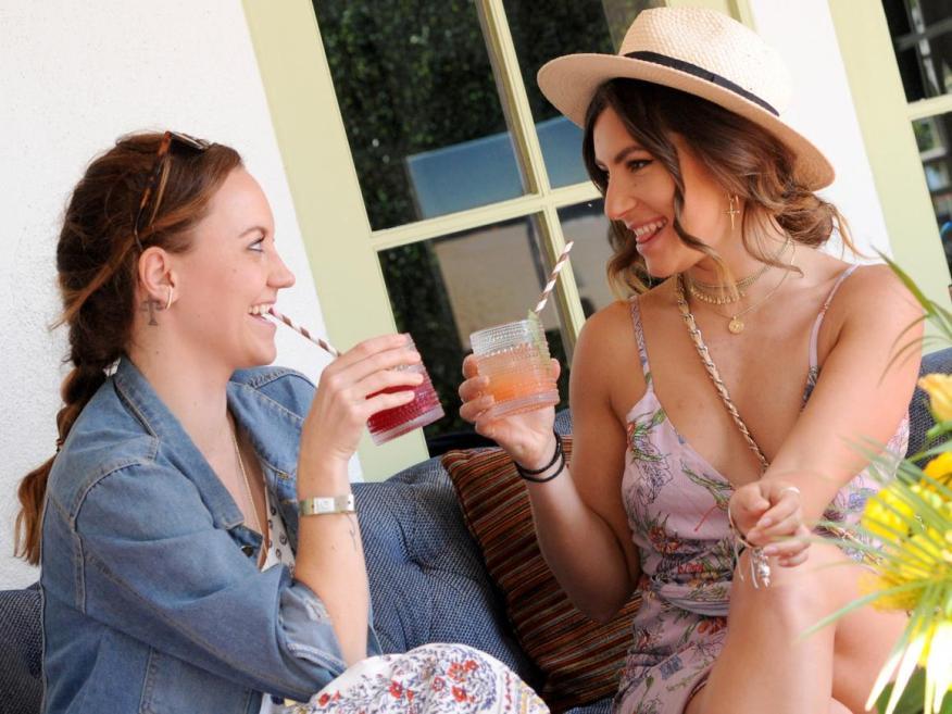 Dos mujeres ociosas tomando unos cócteles.