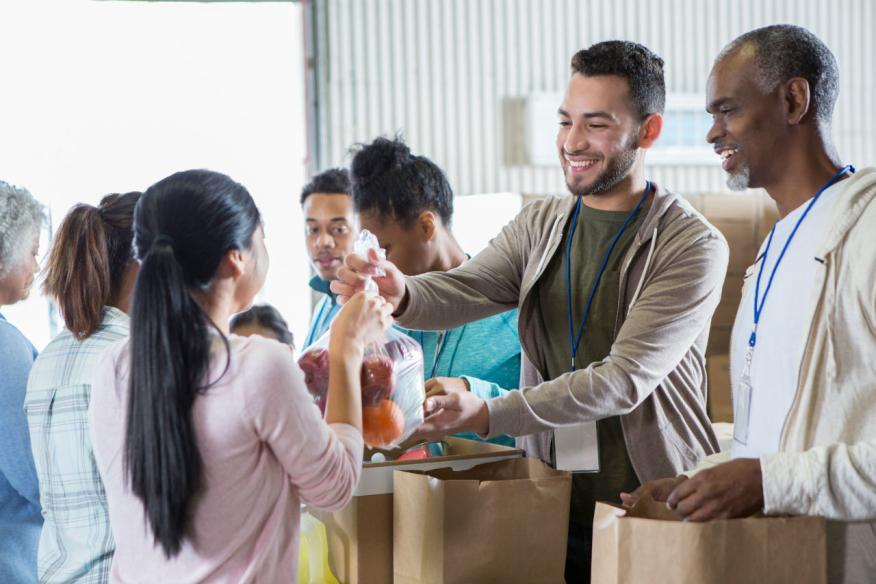 Voluntarios reparten comida en un banco de alimentos