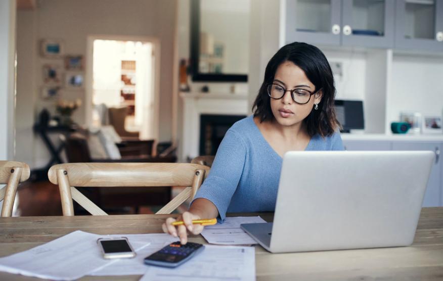 Una mujer hace cuentas con su ordenador y su calculadora