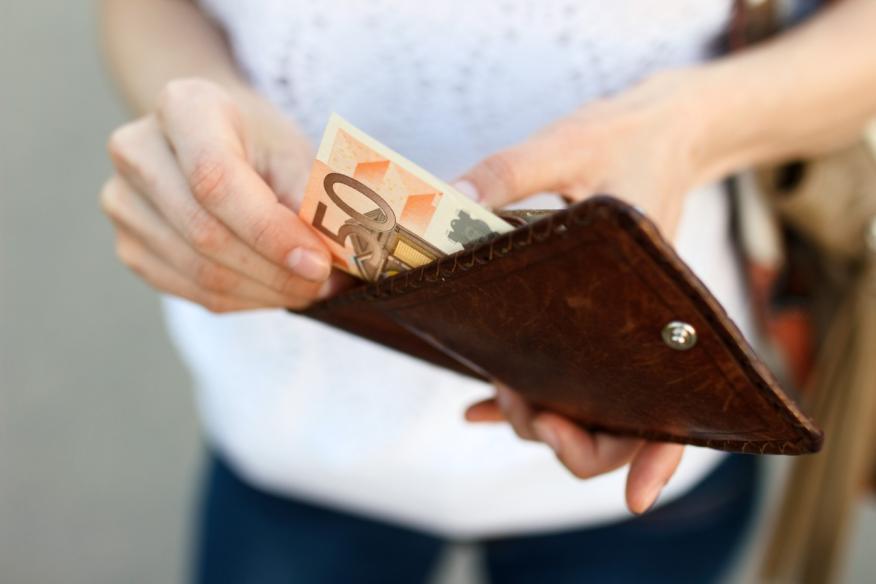 Una mujer saca un billete de 50 euros de su cartera