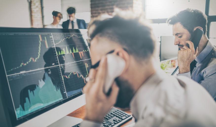 Dos inversores hablan con sus clientes ante una pantalla con gráficas de mercado