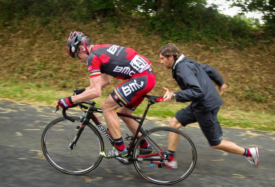 Un ciclista intenta recuperar velocidad con ayuda de un miembro de su equipo