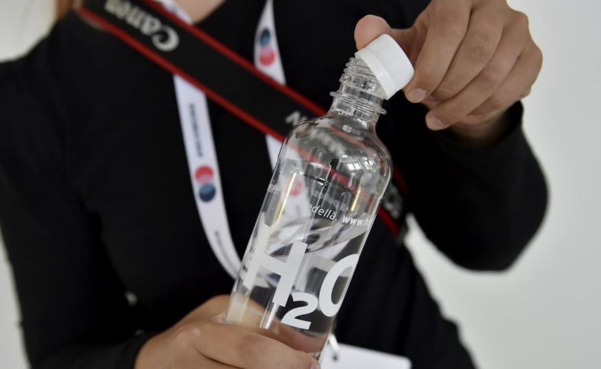 Una mujer sostiene una botella de agua.