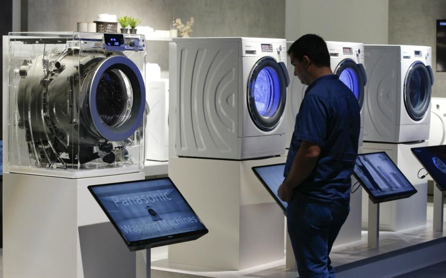Un hombre mira varias lavadoras.