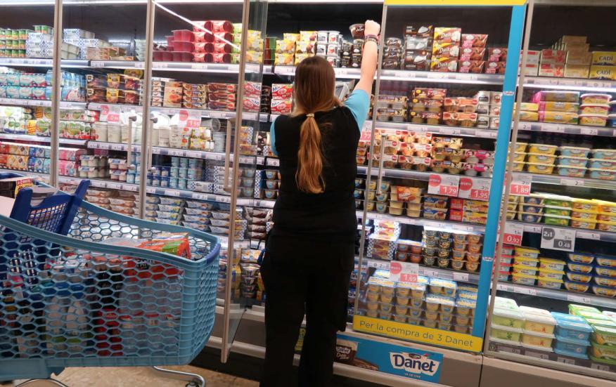 Una mujer coge yogures en un supermercado.
