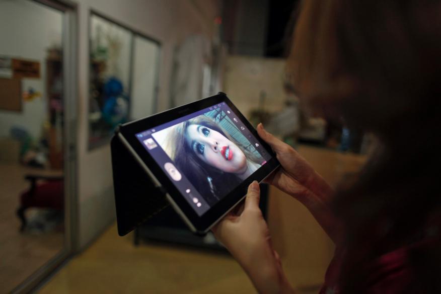 Mujer revisando un vídeo a través de un teléfono móvil