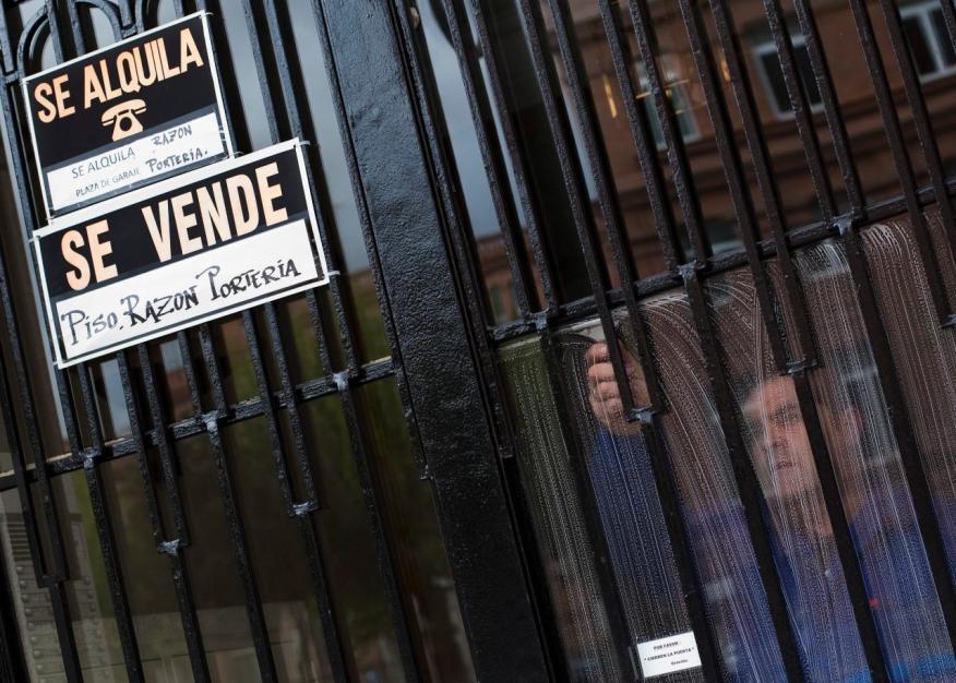 Un portero limpia el portal de un edificio en Madrid con carteles de pisos en venta y en alquiler
