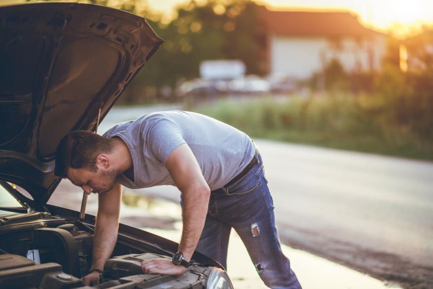 Un conductor revisa el motor de su coche