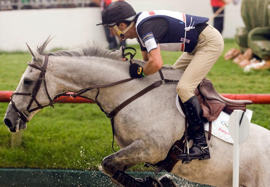 Un jockey salta un obstáculo sobre su caballo en una competición hípica