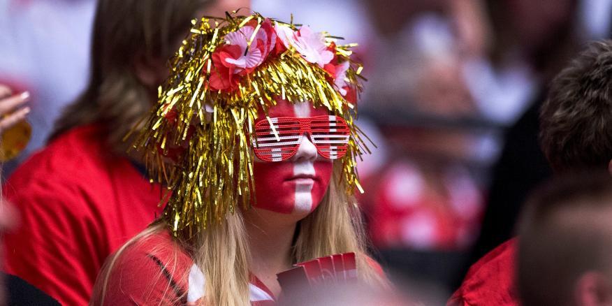 Una mujer con la cara pintada con la bandera de Dinamarca.