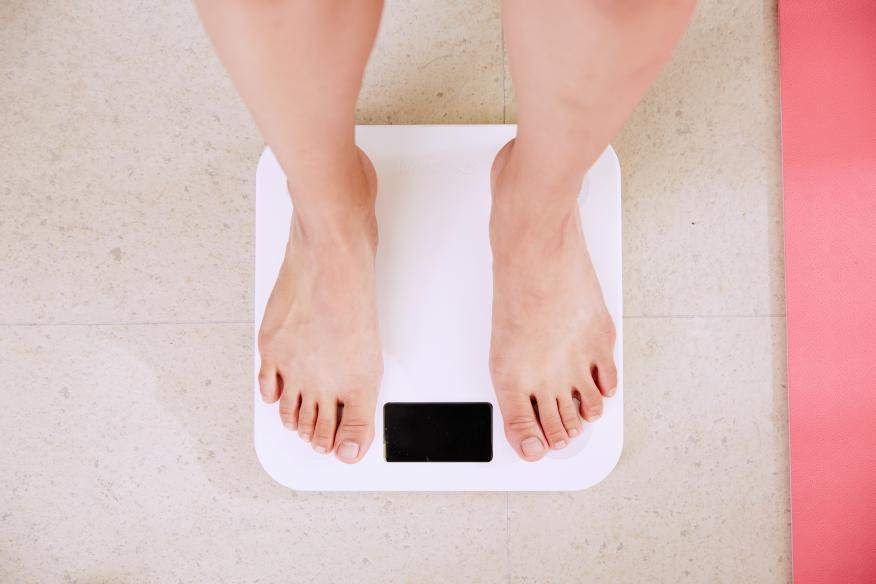 persona pesándose en una báscula. Dieta pérdida de peso