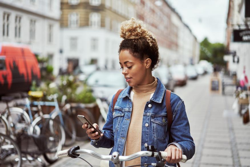 Mujer en bici con el móvil en la mano.