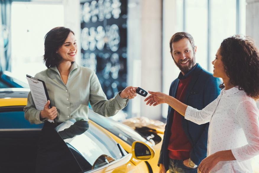 Mujer cogiendo las llaves del coche que se acaba de comprar