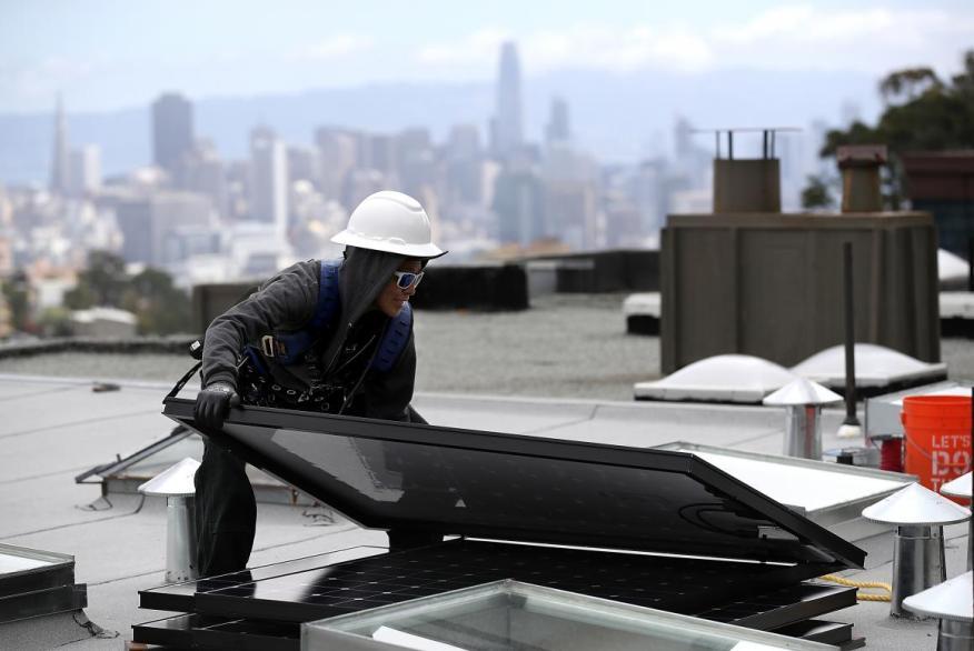 Una mujer mueve un panel solar durante su instalación en un tejado en San Francisco, California.