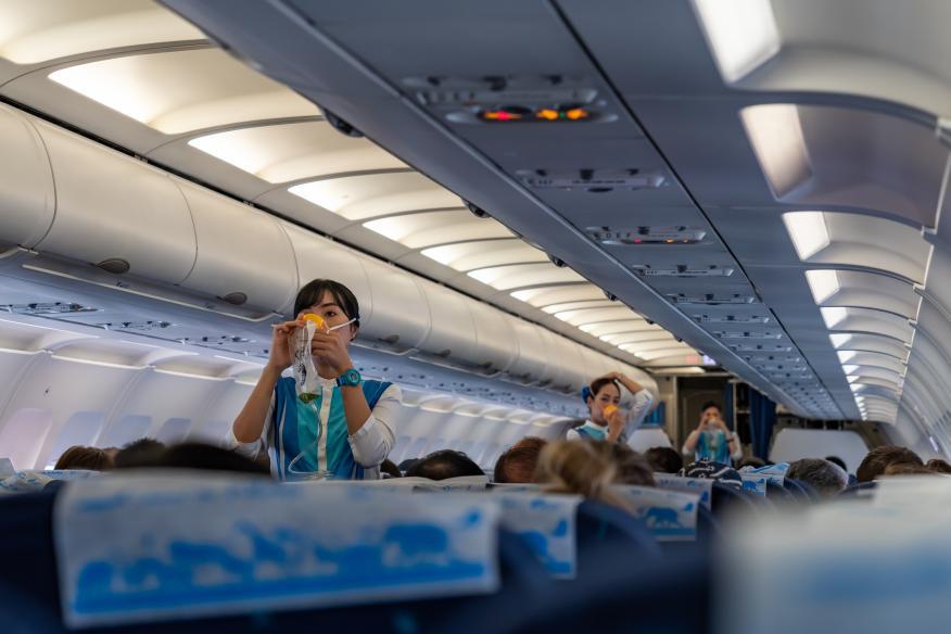 Azafata de vuelo explicando cómo utilizar una mascarilla de oxígeno.