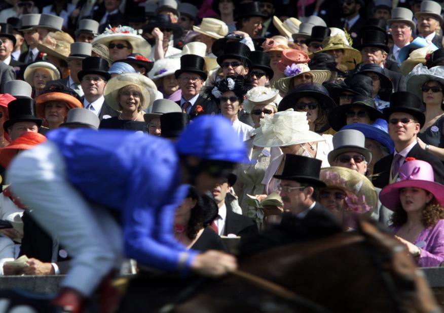 Un grupo de millonarios sigue una carrera de caballos en el hipódromo de Ascot