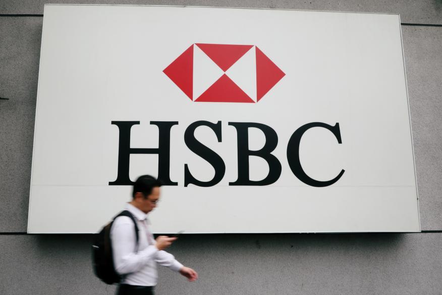 Un hombre camina delante de un cartel de HSBC.