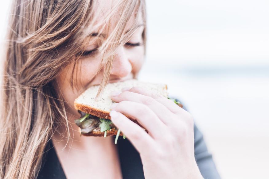 mujer comiendo sándwich, picar entre horas