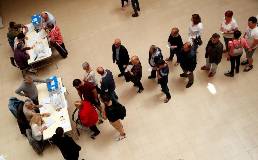 Varias personas hacen cola para votar en un colegio electoral de Barcelona