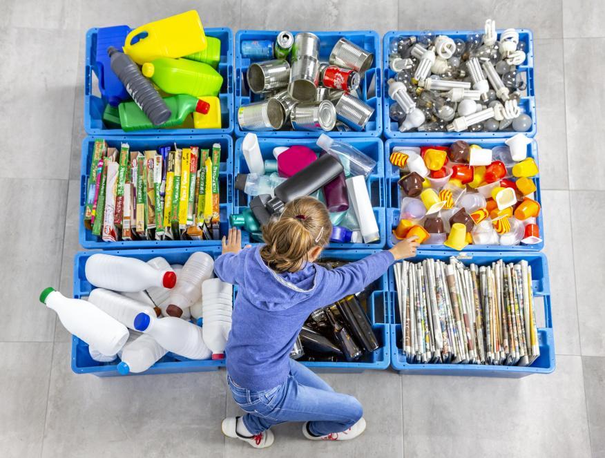 Una niña separa envases para reciclar