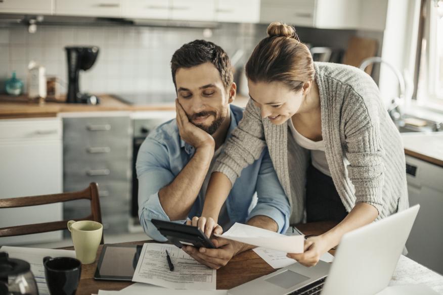 Pareja de millennials calculando ahorros.