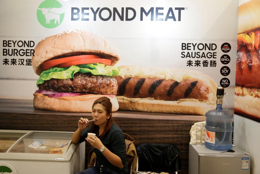 Una mujer junto a un póster del stand de la compañía de alimentos a base de plantas Beyond Meat en la feria VeggieWorld de Pekín.