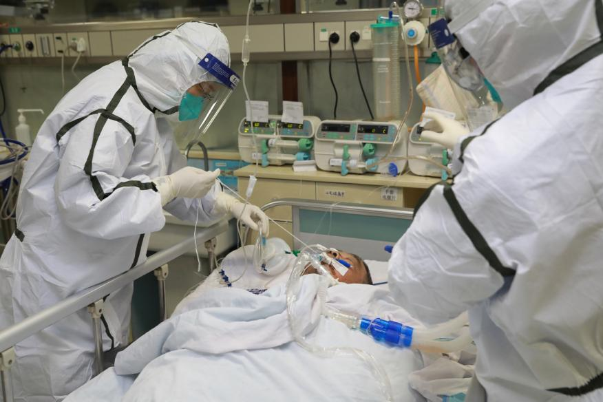 Dos médicos vestidos con trajes protectores tratan a un paciente en un hospital de Wuhan