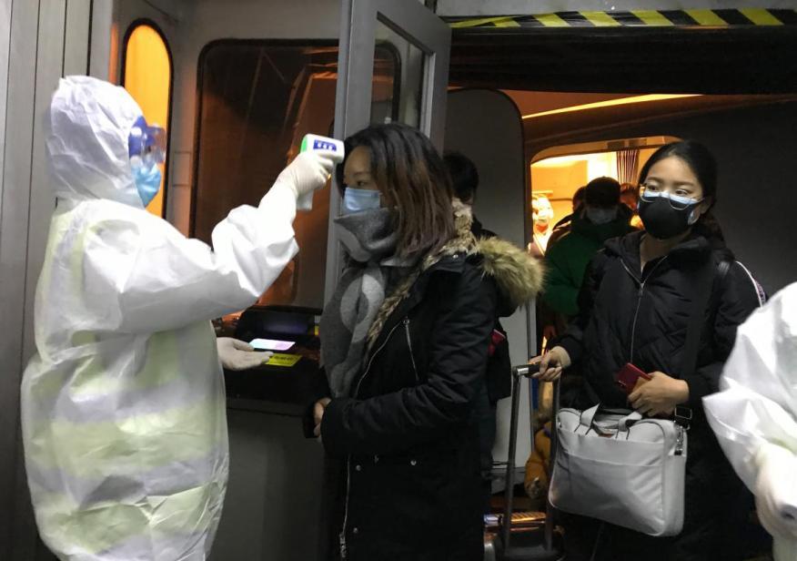 Oficiales sanitarios miden  la temperatura corporal de los pasajeros que llegan de Wuhan, China, el 22 de enero de 2020, en el aeropuerto de Pekín..