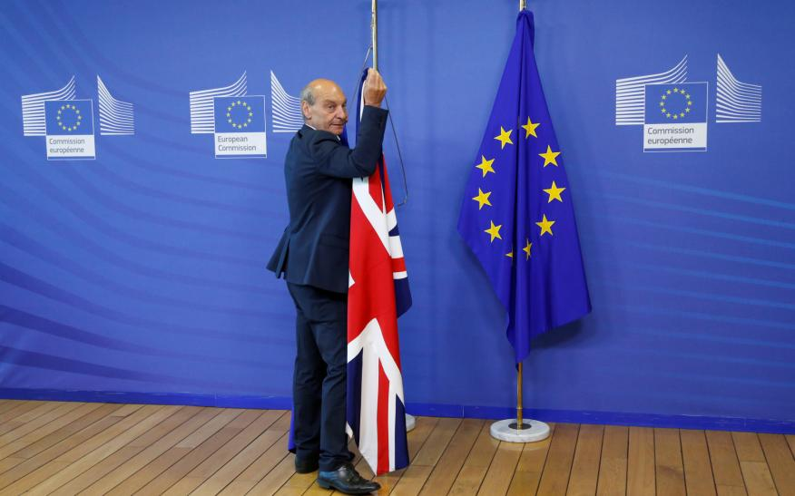 Un trabajador de la Comisión Europea retira la bandera británica