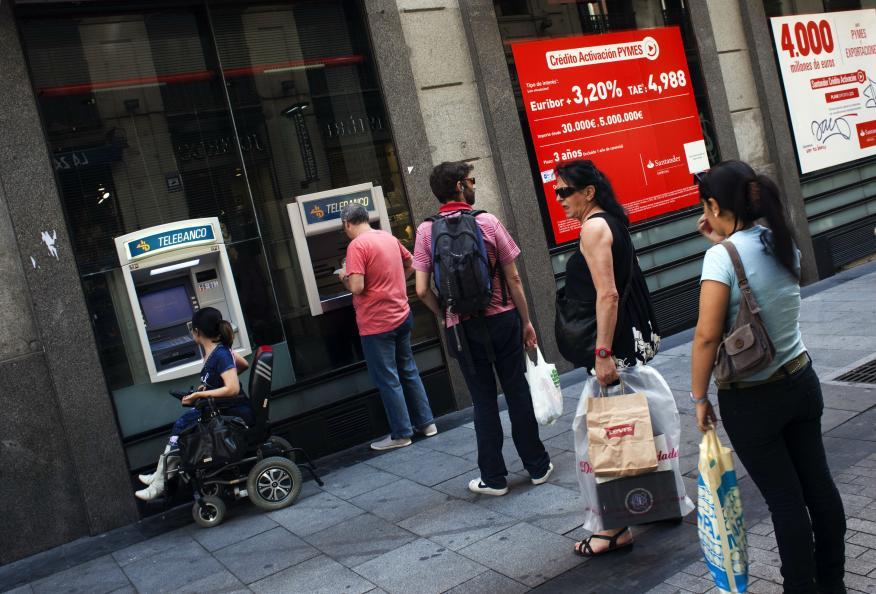Varias personas hacen fila delante de un cajero en Madrid.