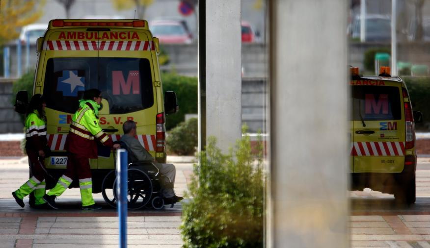 2 técnicos de ambulancias acompañan a un enfermo en silla de ruedas en el hospital de Alcorcón