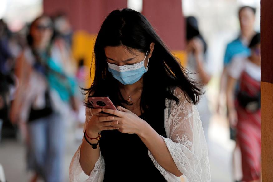Una mujer utiliza su teléfono móvil mientras lleva una mascarilla en Sri Lanka.