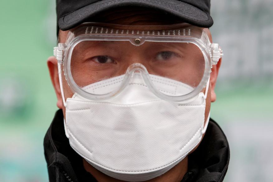 Coronavirus: Un trabajador de una fábrica en Pekín se protege con una mascarilla