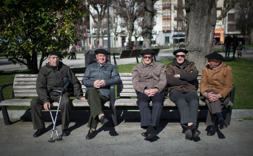 Un grupo de jubilados toma el sol en un banco de Bermeo