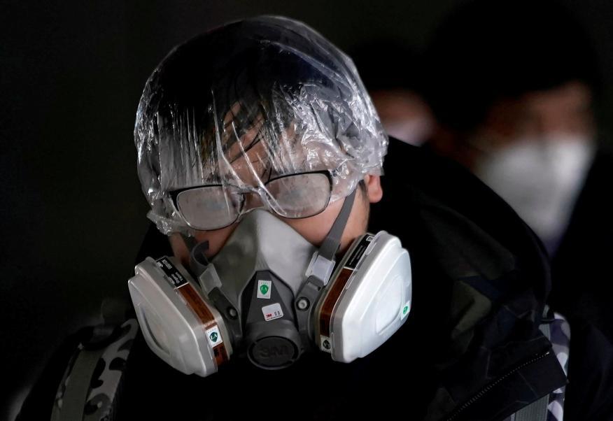 Un hombre utiliza una máscara protectora para protegerse durante la propagación del brote del coronavirus