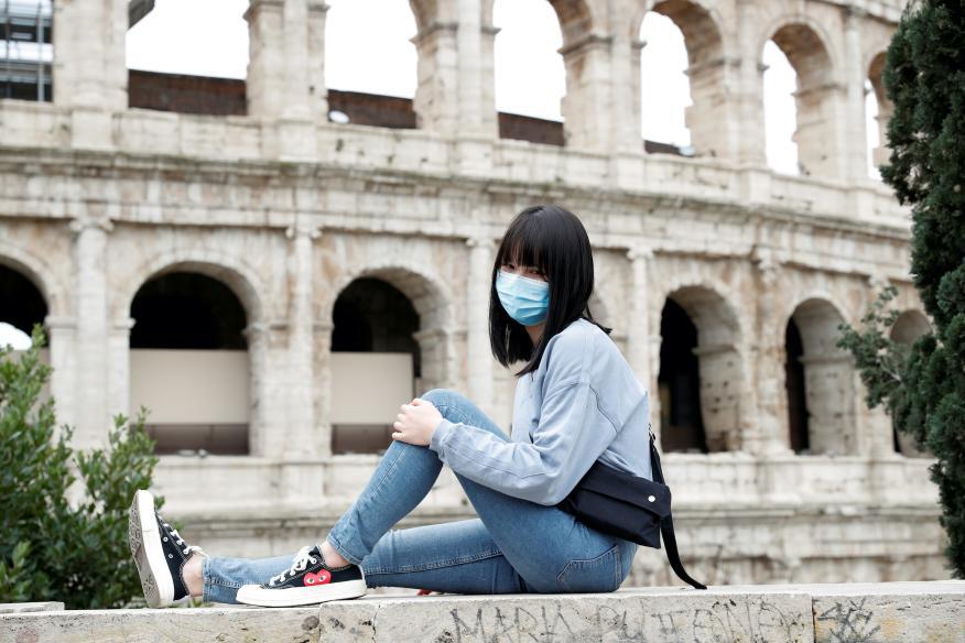 Una turista con una mascarilla posa ante el Coliseo de Roma, en Italia.