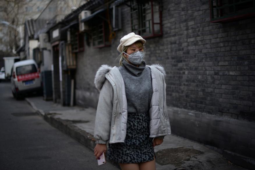 Mujer pasea por las calles de China ante el coronavirus.