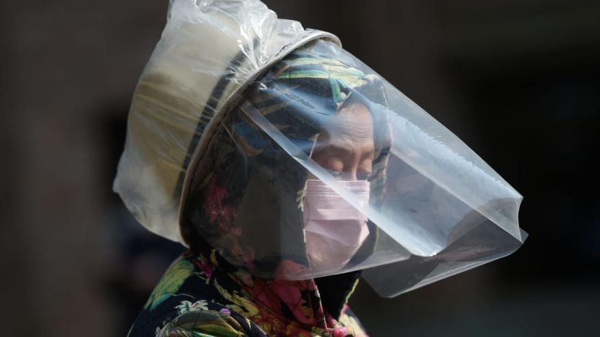 Una mujer se protege la cara con mascarilla en Wuhan, China, epicentro del coronavirus