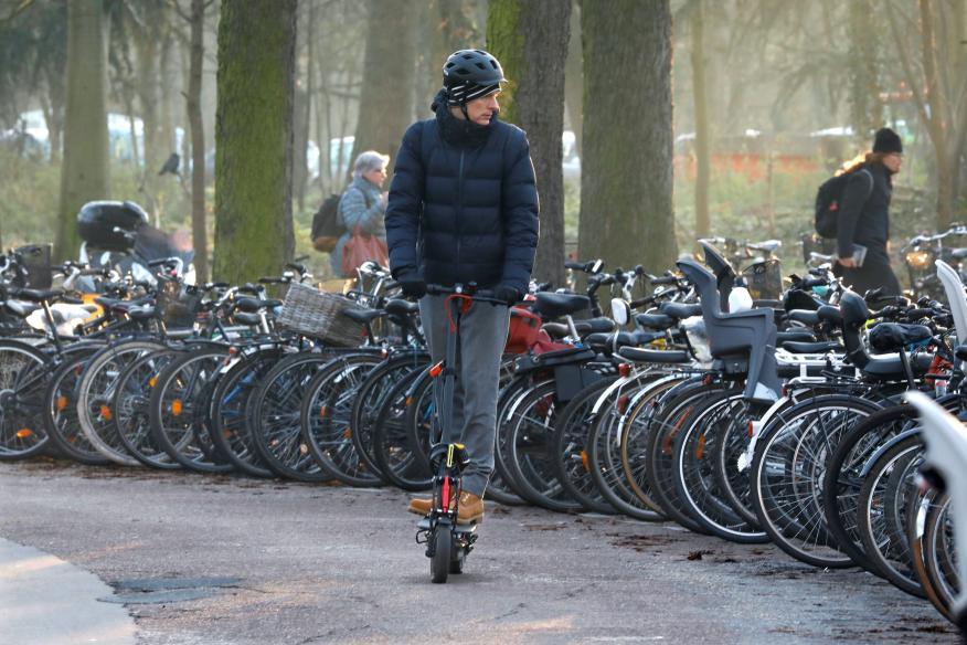 Un hombre que conduce un patinete eléctrico compartido pasa por un aparcamiento de bicis en París, Francia.