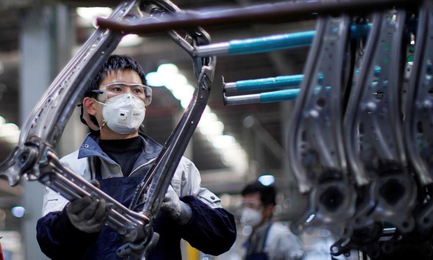 Un trabajador ensambla piezas de asientos de coche en una fábrica en Shanghai