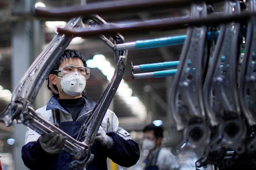 Un trabajador de una fábrica en Shanghái con una mascarilla por miedo a los contagios por el coronavirus
